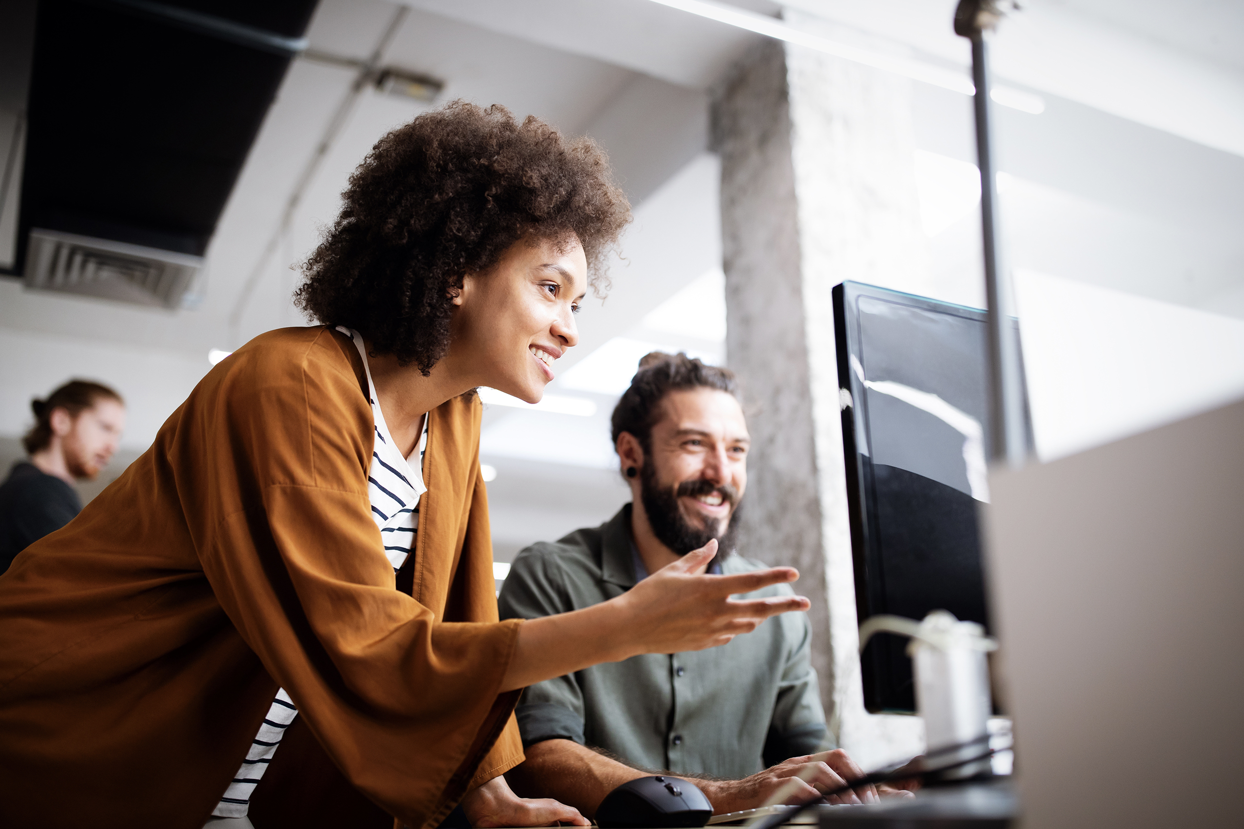 WOman helping man with computer IT problem