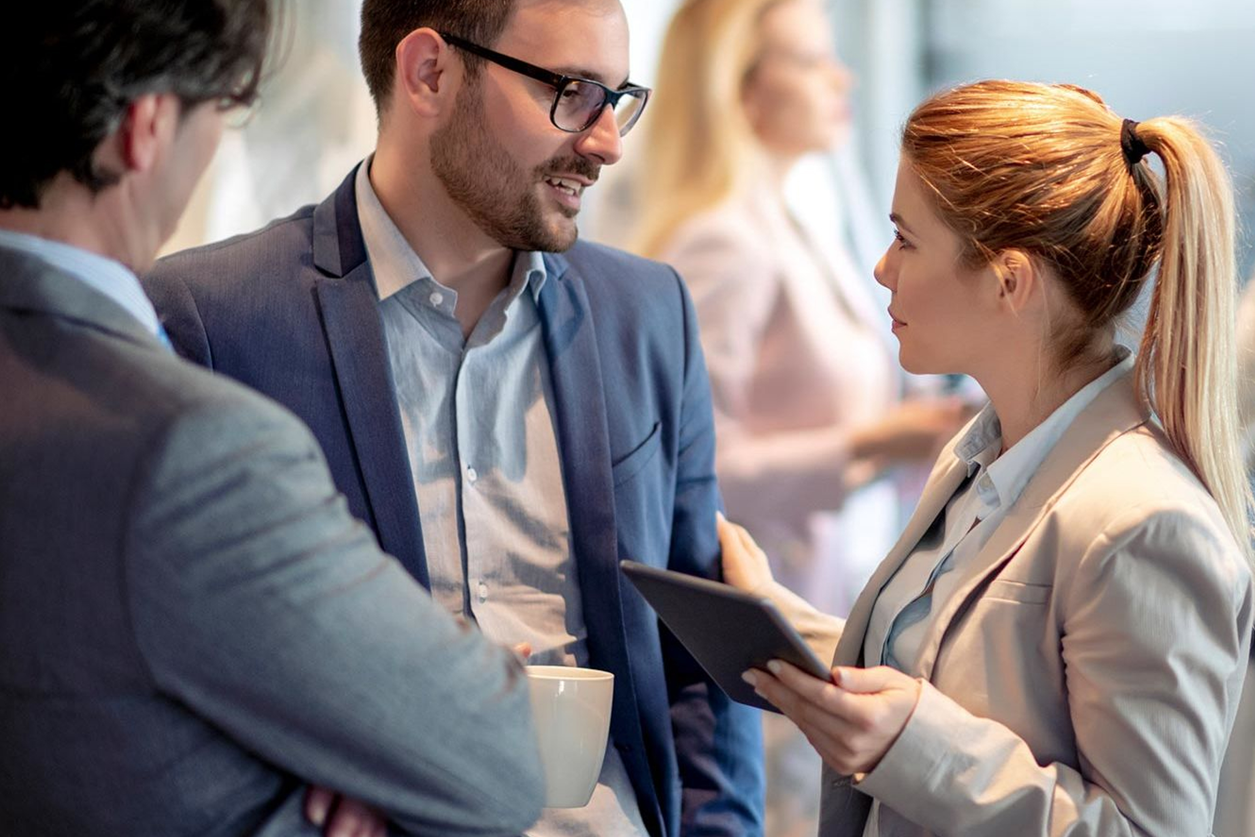 Woman with tablet talking to man about business