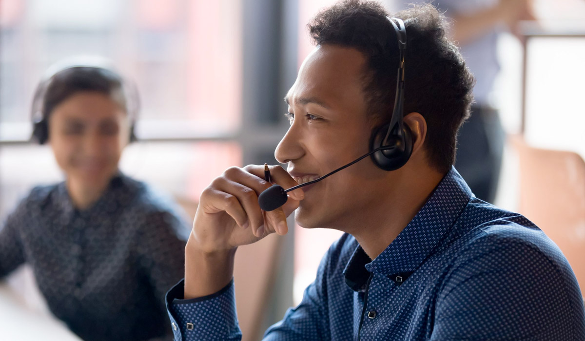 Smiling young businessman call center agent at workplace