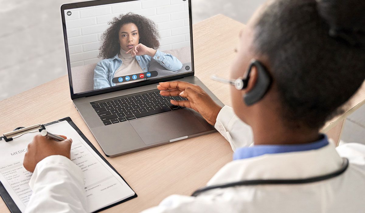 black female doctor chatting with patient over video conference