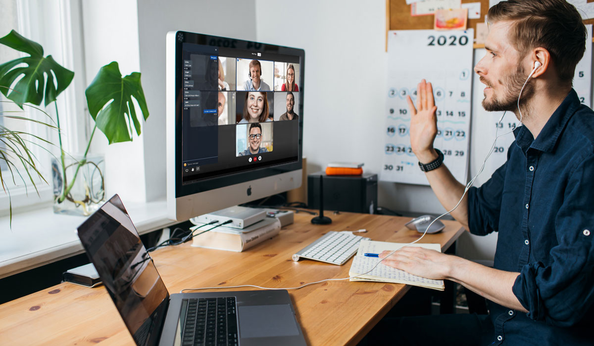 guy working from home waving to colleages on video conference chat